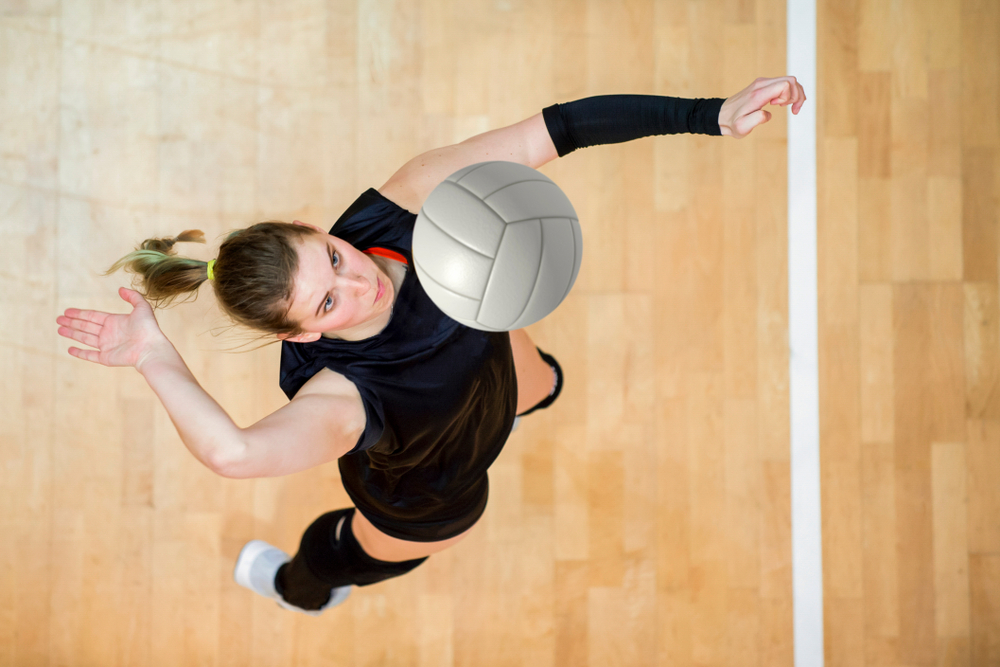 Volleyball player jumping in air to serve ball